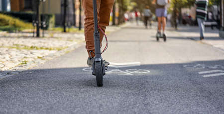 Young man in casual trousers riding an electric scooter detail on his feet and wheel over asphalt road