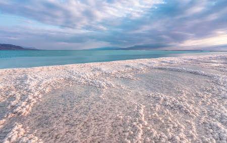 Morning sun shines on salt crystals formations, clear cyan green calm water near, typical landscape at Ein Bokek beach, Israel