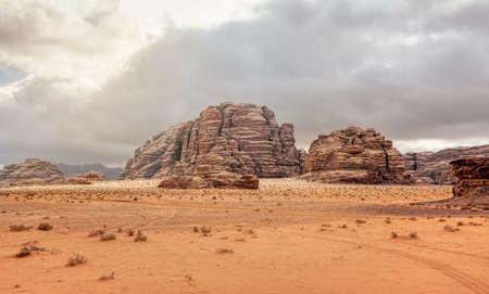 Rocky massifs on red orange sand desert, overcast sky in background - typical scenery in Wadi Rum, Jordan 版權商用圖片