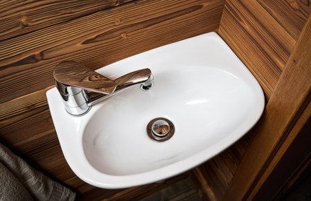 Small white wash basin, wooden walls around, closeup detail