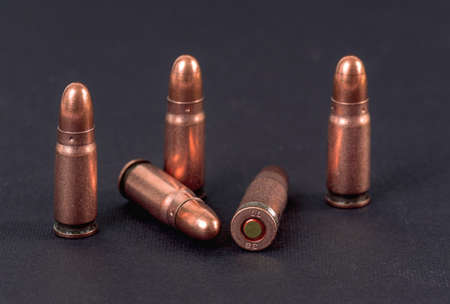Five bronze pistol bullets on black board, closeup detail 版權商用圖片