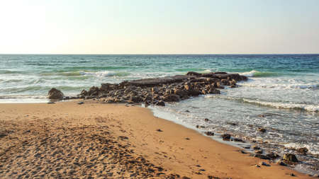 Empty beach with footsteps, some rocks in sea, in evening few moments before sunset. Lapta, Northern Cyprus