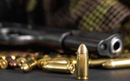 Single yellow brass bullet detail, black metal gun in background Banque d'images