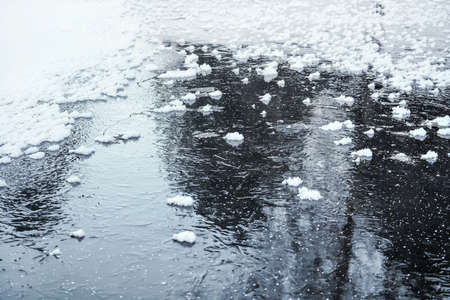Ice on frozen pond with small patches of snow crystals, tree reflection on surface