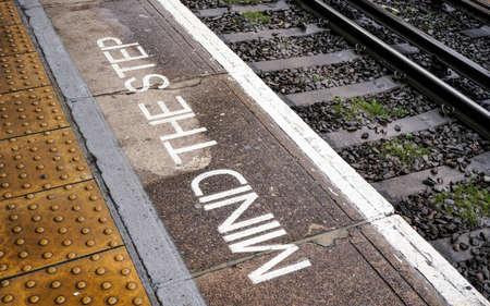 MIND THE STEP written on train platform near rails at London DLR ( Docklands Light Railway ) station