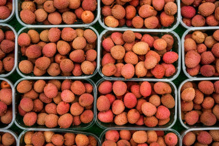 Overhead shot - lychee fruits in small plastic boxes, displayed on food market at Lewisham, London Фото со стока