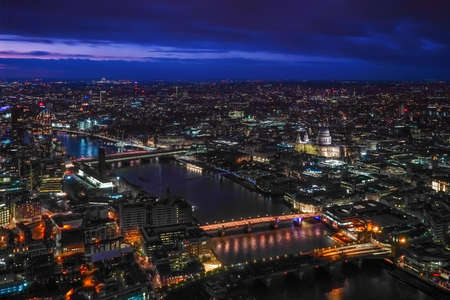 Aerial view of north east part of London, in evening. St Pauls Cathedral visible over river Thames.
