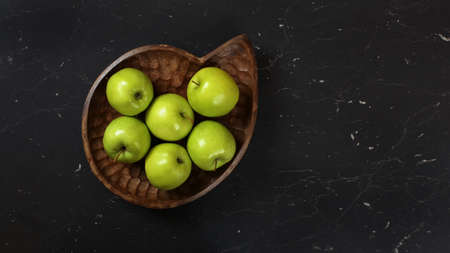 Green apples in wooden carved bowl on black working board, photographed from above.