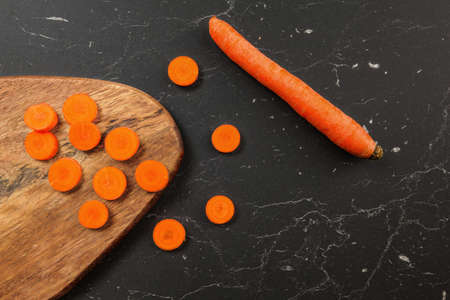 Carrot sliced to small circles and chopping board, whole one next to it on black working desk, photo from above
