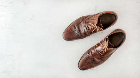 Overhead shot, pair of old worn brown shoes on white board, wide banner with space for text left Фото со стока