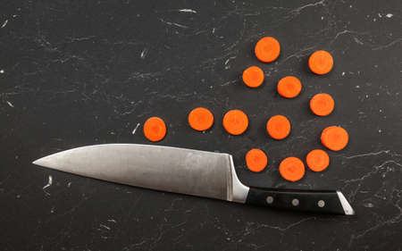 Top down view, chefs knife and small circles of sliced carrot on black marble like working board.
