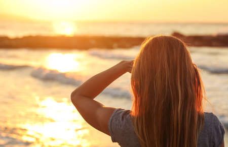 Sporty woman watches sunset over the sea, shading her eyes with one hand, view from behind only hair visible