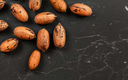 Whole pecan nuts on black marble board, flat lay photo with space for text down right Фото со стока