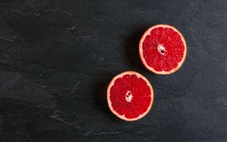 Flat lay photo - pink grapefruit cut in two halves, on black slate board