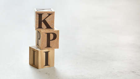 Pile with three wooden cubes - letters KPI meaning Key Performance Indicator on them, space for more text / images at right side.