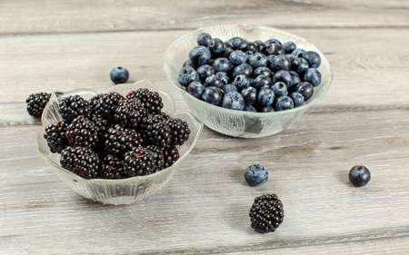 Small glass bowl of blueberries and blackberries on gray wood desk
