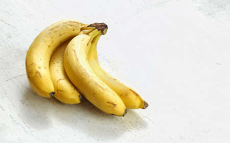 Bunch of ripe bananas on white working board. Фото со стока