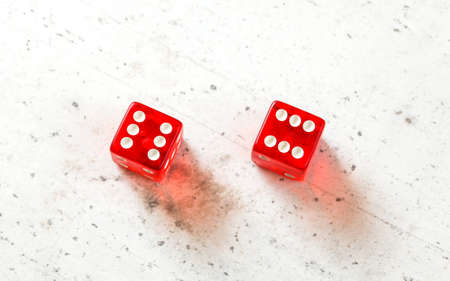 Two red craps dices showing Boxcars or Midnight (double number six) overhead shot on white board