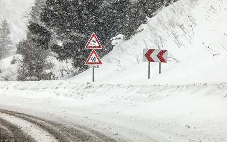 Sharp curve on road, with road signs (careful skid, snow) during heavy snowstorm blizzard in winter. Dangerous driving conditions.
