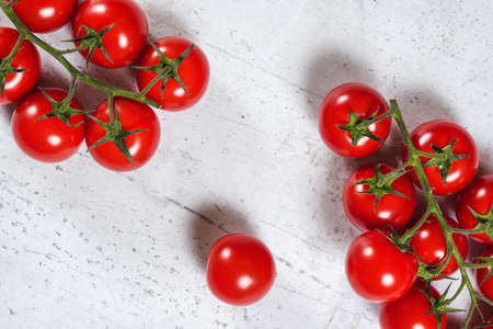 Vibrant small red tomatoes with green vines on white stone like board, view from above Stock fotó