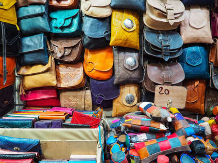 Handmade colourful leather bags and purses on display at traditional souk - street market in Morocco