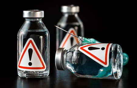 Vaccine bottles with red triangle exclamation mark sign on label, black background