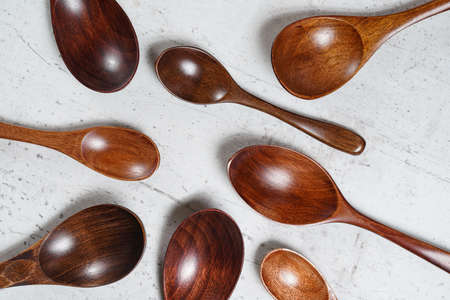 Small spoons made of dark wood, on white working board, view from above Stock fotó