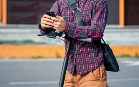 Young man wearing shirt leaning on electric scooter handlebar, holding mobile smartphone in his hands, closeup detail