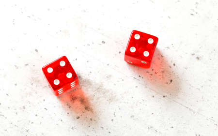 Two red craps dices showing Hard Eight from Decatur (double number four) overhead shot on white board