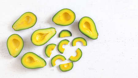 Top down view, avocado half and slices, on white working board, fruit pulp has vibrant green and yellow colour, space for text right. Stock fotó