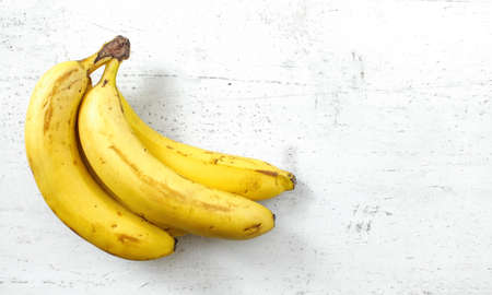 Bunch of bananas on white working board, space for text right
