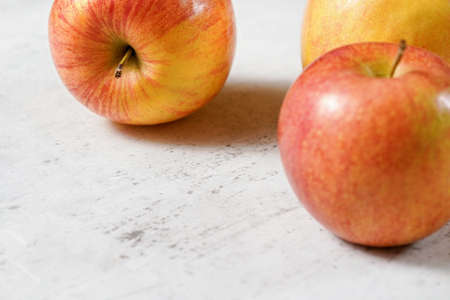 Red and yellow apples (kiku variety) on white board, closeup whit space for text down left.