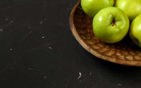 Green apples on wooden carved bowl, only part visible at black board - wide banner with space for text left