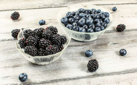 Blueberries and blackberries in glass bowls, some of them spilled on gray wood desk. Stock fotó