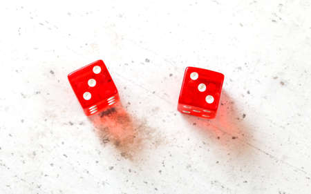 Two red craps dices showing Hard Six (double number three) overhead shot on white board Stock fotó