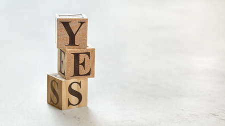 Pile with three wooden cubes - word YES on them, space for more text / images at right side.