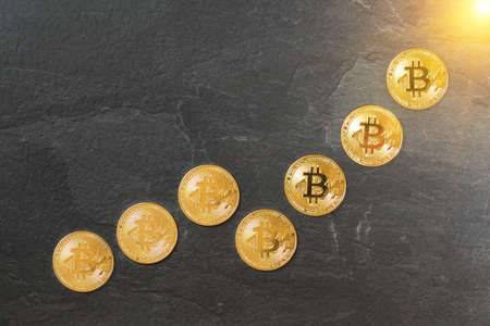 Rising chart made of gold bitcoin coins, concept of cryptocurrency value growing to the moon / sun Stock fotó