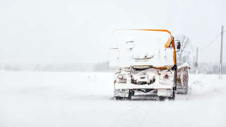 Orange plough truck on snow covered road, gray sky and trees in background, view from car driving behind Stock fotó
