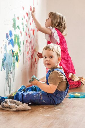 Two siblings are painting on wall with fingers. They have big fun. Boy has kid dungarees.