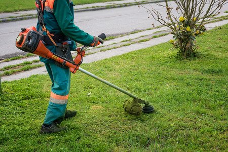Man in overall and safety helmet trims overgrown grass by grass cutter Archivio Fotografico