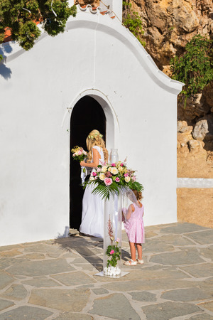 Bride in white wedding dress in front of chapel ready for ceremony in St. Paul´s bay on Rhodes, Greece