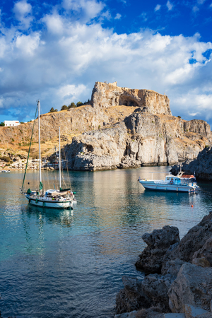 Sail boats in St. Paul´s bay, cloudy blue sky, Lindos acropolis in background (Rhodes, Greece) Stock Photo