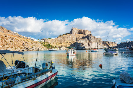 Fishing boats and sail boat in St. Paul´s bay, Lindos acropolis in background (Rhodes, Greece)