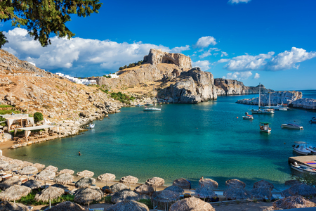 Beautiful St. Paul´s bay with boats, Lindos acropolis in background (Rhodes, Greece)