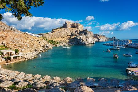 Schöne St. Pauls Bucht mit Booten, Lindos Akropolis im Hintergrund (Rhodos, Griechenland)