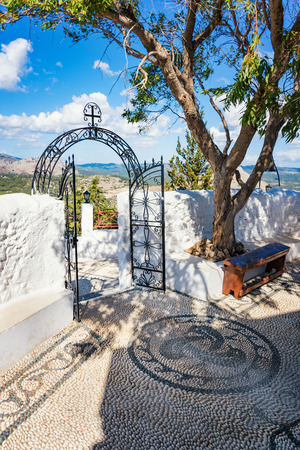 Iron gate and bronze bell in Tsambika Monastery, (RHODES, GREECE)