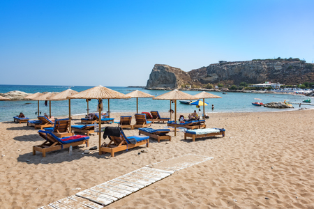 Stegna beach with sunshades and sunbeds, boats in background (RHODES, GREECE) Editorial