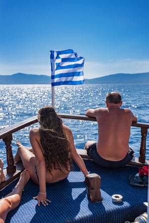 Young girl and man sun bathing in front of Greek flag on boat deck (RHODES, GREECE)
