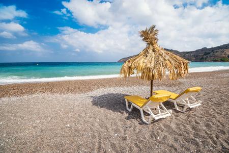 Empty sunbeds and umbrella on Vlycha beach near Lindos village (Rhodes, Greece) 版權商用圖片