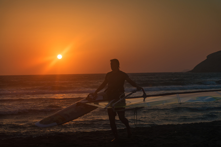 Windsurfer with his surf getting out of water on Prasonisi beach, sunset (Rhodes, Greece)